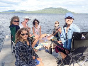 happy-group-of-women-sitting-on-dock