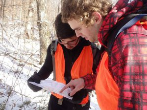 men-reading-map-hiking-with-orange-vests